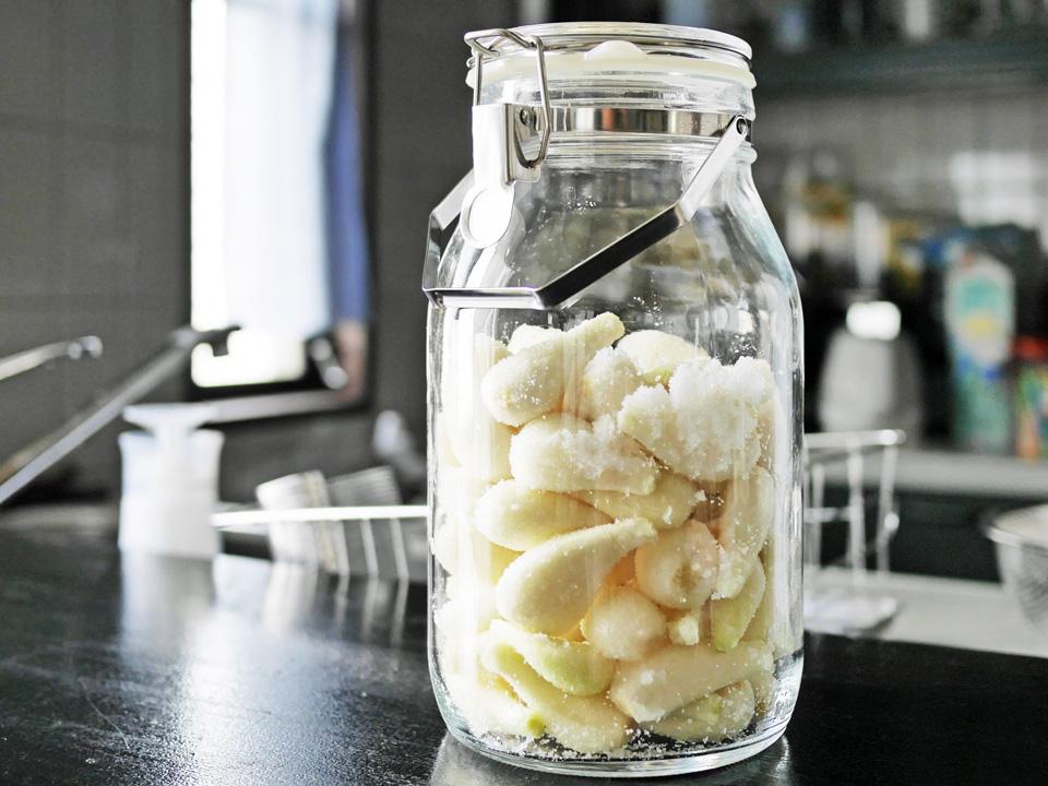 粗塩をまぶしたらっきょうを密封ビンで発酵させる