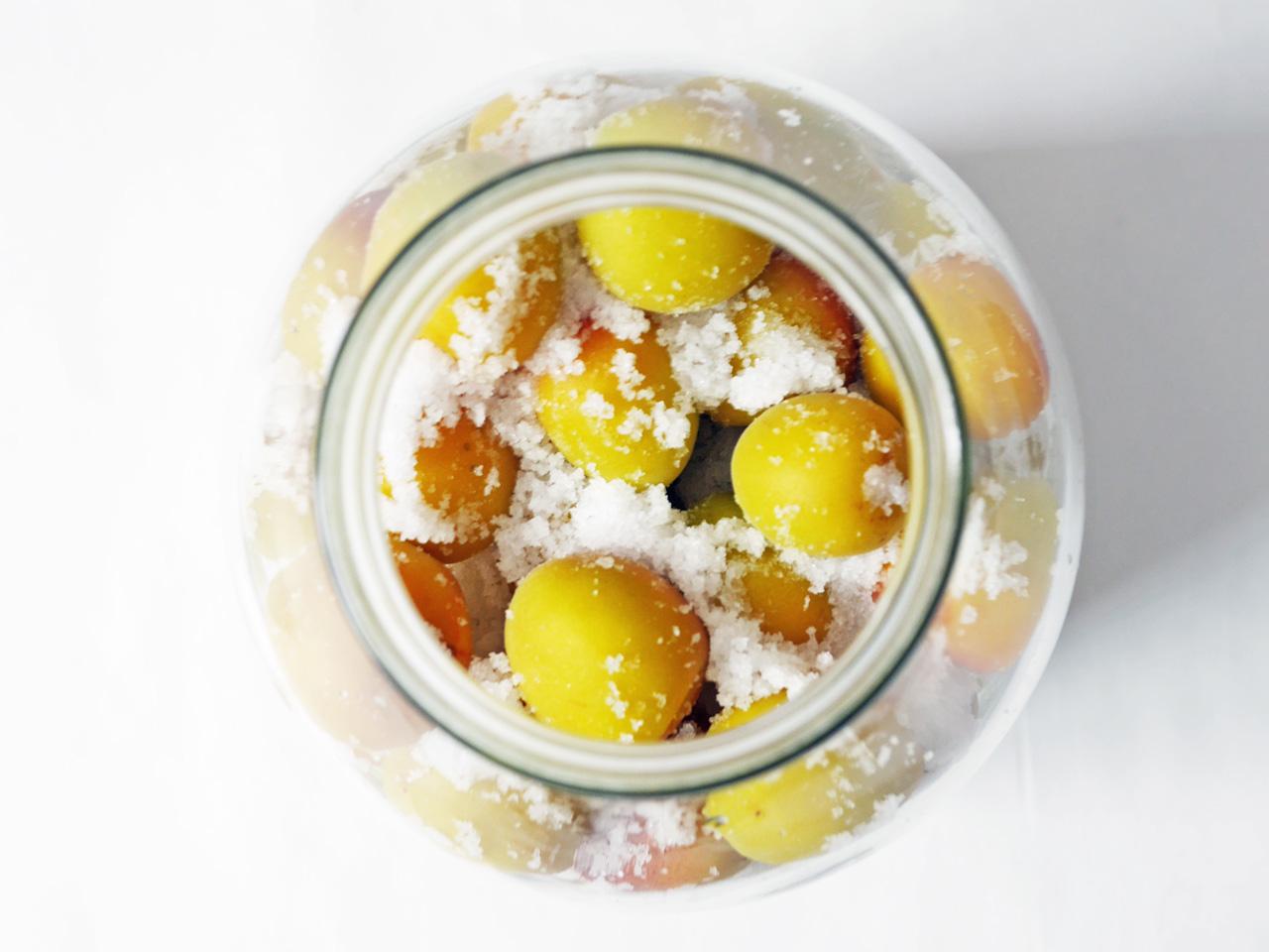 密封瓶に粗塩と梅を交互に入れていく